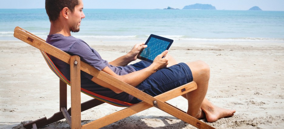 Man online banking from a tablet at the beach